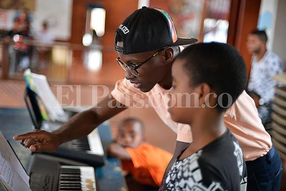 En la foto Junior Zamora dando clases de piano a sus estudiantes del Centro Cultural 'Abriendo Puertas' en Aguablanca.<br>Foto: Jorge Orozco | El País